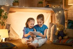Children are playing with tablet in tent. Cute little children are playing with tablet in tent. Happy girls at home. Funny lovely kids having fun in room royalty free stock photo