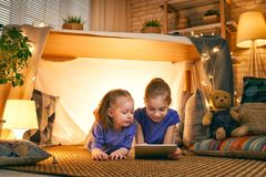 Children are playing with tablet in tent. Cute little children are playing with tablet in tent. Happy girls at home. Funny lovely kids having fun in room royalty free stock images