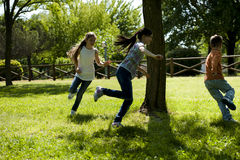Children playing tag. Small group of children playing running around a tree, playing tag royalty free stock photography