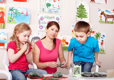 Children playing with teacher from clay. Royalty Free Stock Photography
