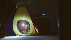 Children Are Playing In A Tent With Flashlights.