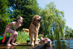 Children playing with their dog on a lake Royalty Free Stock Photography