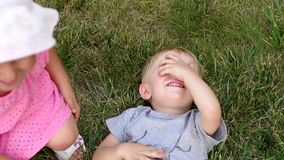 Children playing tickle on the grass in the park. A little boy lies on the grass in the park and covers his face with his hand, and his little sister tickles stock video