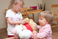 Children playing together. Two cute children playing together at home with soft toys stock image