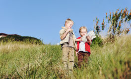 Children playing together. Brother and sister children playing pretend adventure game outdoors having fun in the field stock images