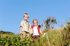 Children playing together. Brother and sister children playing pretend adventure game outdoors having fun in the field stock photo