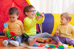 Children playing together at home. Two girls and boy with toys on  floor at home Royalty Free Stock Photos