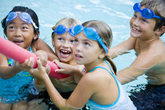 Children playing together with pool toy royalty free stock photo