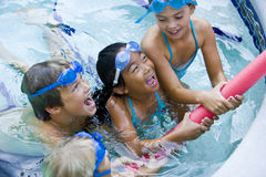 Children playing together with pool toy. Four kids playing tug of war with pool toy, 7 to 9 years Royalty Free Stock Image