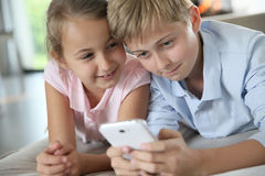 Children playing together on smartphone Stock Photography