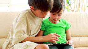 Children playing together with a tablet computer. In the living room stock footage