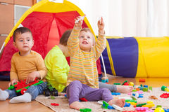 Children playing together. Three children playing on  floor with colored toys Royalty Free Stock Photography