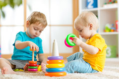Children playing together. Toddler kid and baby play with blocks. Educational toys for preschool kindergarten child