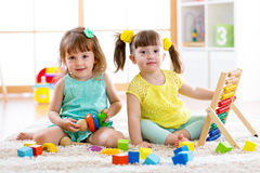 Children playing together. Toddler kid and baby play with blocks. Educational toys for preschool and kindergarten child. Little gi Royalty Free Stock Photography
