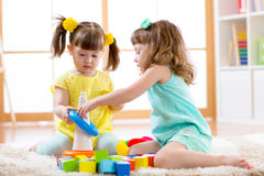 Children playing together. Toddler kid and baby play with blocks. Educational toys for preschool and kindergarten child. Little girls building pyramid toys at Stock Image