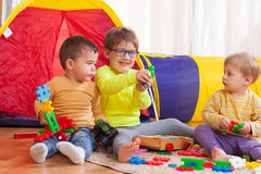 Children playing together. Two girls and boy with toys on  floor at home Royalty Free Stock Image