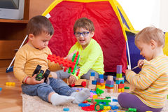 Children playing together. Two girls and boy with toys on  floor at home Royalty Free Stock Photos