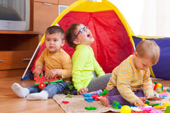 Children playing together. Two girls and boy with toys on  floor at home Royalty Free Stock Photography