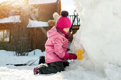 Children playing together in yard after snowfall in winter. Group of kids bilding figures and snowman with shovels and other tools. Outdoors. Child winter royalty free stock photo
