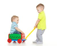 Children are playing with toy car. Children are playing with toy handcart on a white background. One little boy sits in handcart, another child pulls him. Merry royalty free stock photos