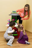 Children playing with toy cooker. Two young girls and boy playing with plastic toy cooker in room Stock Image