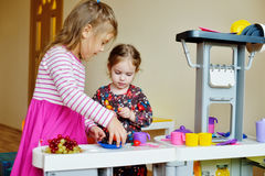 Children  playing toy kitchen Stock Photography