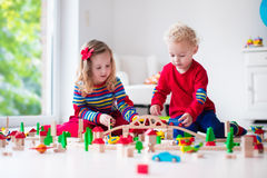 Children playing with toy railroad and train. Children playing with wooden train. Toddler kid and baby play with blocks, trains and cars. Educational toys for Royalty Free Stock Photography