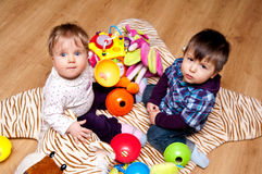 Children playing with toys. High angle view of baby girl and preschool boy playing with toys on tiger striped rug Royalty Free Stock Photography