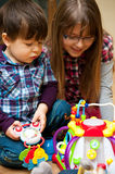 Children Playing with Toys. Brother and sister playing together on the floor with toys Stock Image