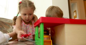 Children playing toys on floor in game room. Smart curiosity children playing with plastic car and toy in light game room stock footage