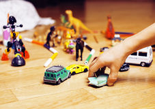 Children playing toys on floor at home, little hand in mess, fre Stock Photos