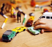 Children playing toys on floor at home, little hand in mess, free education. Concept Stock Images