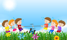 Children playing tug o war in the field Royalty Free Stock Photo