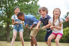 Children playing tug of war. At the park stock image