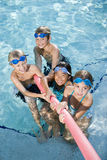 Children playing tug of war in pool. Multiracial friends tugging on pool toy in swimming pool, ages 7 to 9 Royalty Free Stock Images