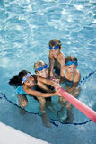 Children playing tug of war in pool. Multiracial friends tugging on pool toy in swimming pool, ages 7 to 9 Royalty Free Stock Photography