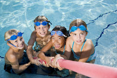Children playing tug of war in pool. Multiracial friends tugging on pool toy in swimming pool, ages 7 to 9 Royalty Free Stock Photos