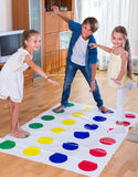Children playing twister at home Stock Photos