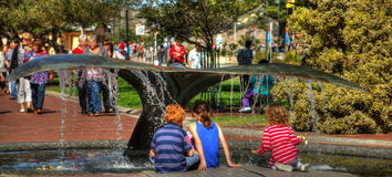 Children playing under whale tail fountain stock photos