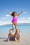 Children Playing on Vacation. A group of Happy Children builds a human pyramid while playing in the ocean on vacation Stock Images