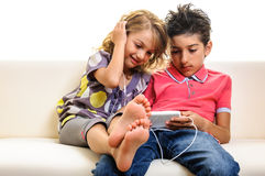 Children playing video games on cell phone Royalty Free Stock Images