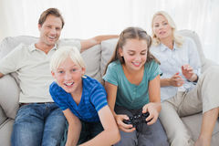 Children playing video games on the couch Stock Image