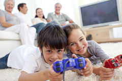 Children playing video games and family on sofa. Children playing video games on floor and family sitting on sofa Royalty Free Stock Image