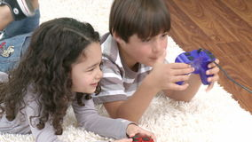 Children playing video games in the livingroom. Footage in high definition of happy children playing video games on the floor at home stock video footage