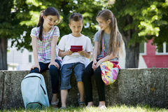 Children playing video games outdoors. Group of Children playing video games outdoors Royalty Free Stock Images
