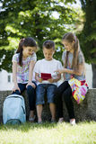 Children playing video games outdoors. Group of Children playing video games outdoors Royalty Free Stock Photos