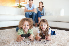 Children playing video games while their parents are watching. In their living room stock photo