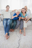 Children playing video games together sitting on the couch. While parents are watching them royalty free stock photos