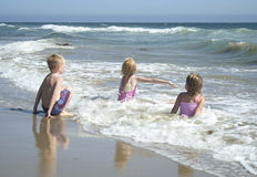 Children playing in the water at the beach royalty free stock photography