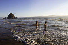 Children Playing in the Water at Cannon Beach. Two children playing in the water at Cannon Beach, Oregon just before sunset, with Haystack Rock in the background Royalty Free Stock Photography
